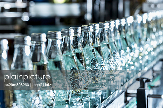 Row of mineral water bottles on conveyor belt