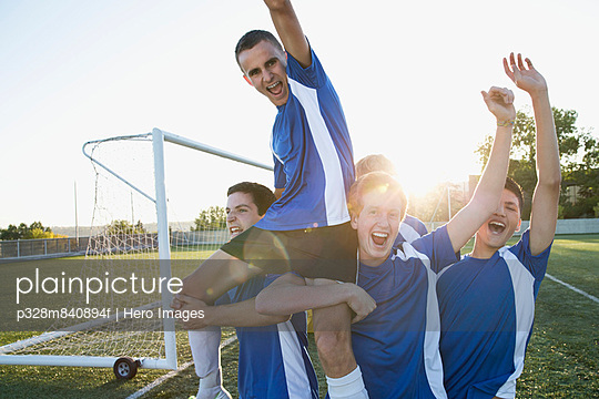 Soccer team lifting teammate after game.