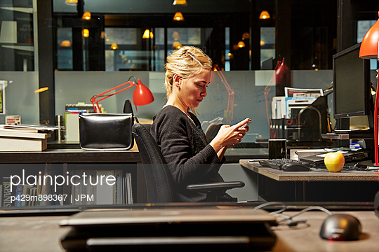 Female office worker at desk using cell phone