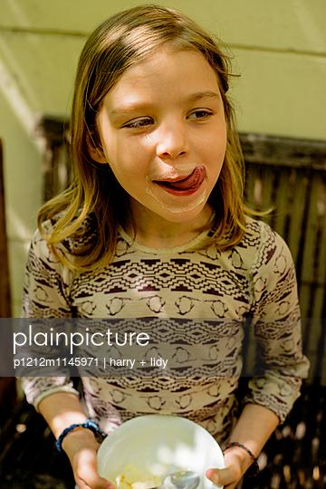 Mädchen isst Eis im Garten - p1212m1145971 von harry + lidy