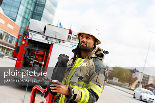 Sweden, Sodermanland, Sodertalje, Male fire-fighter holding fire hose