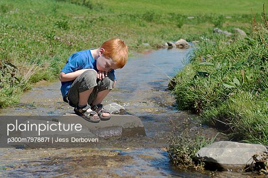 Boy sitting on rock at brook