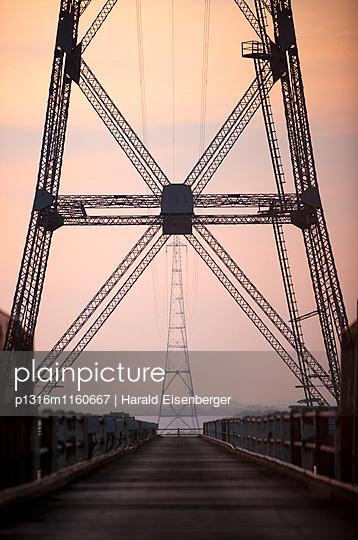 Strommasten an einer Brücke im Sonnenuntergang, Wales, Großbritannien - p1316m1160667 von Harald Eisenberger