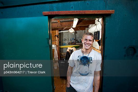 Portrait of attractive male board shaper at his shop.