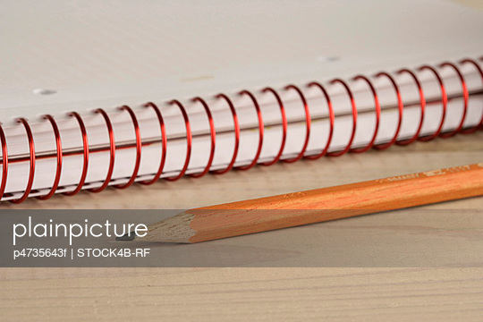 Pencil beside a writing pad