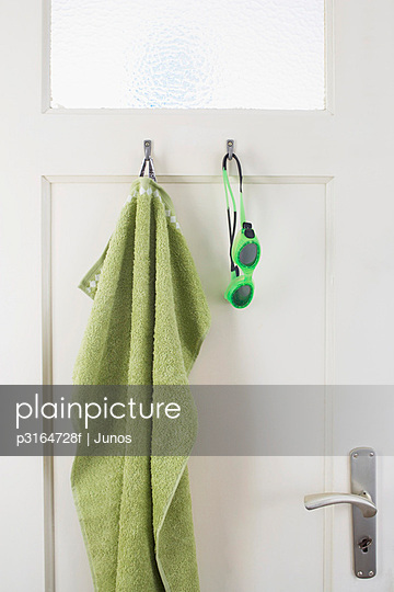 green towel and swimming goggles hanging on bathroom door