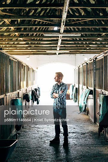 Mann steht im Pferdestall - p586m1146664 von Kniel Synnatzschke