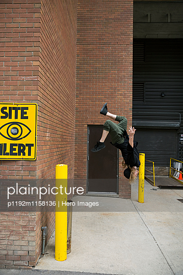 Young man doing parkour backflipping off urban brick wall