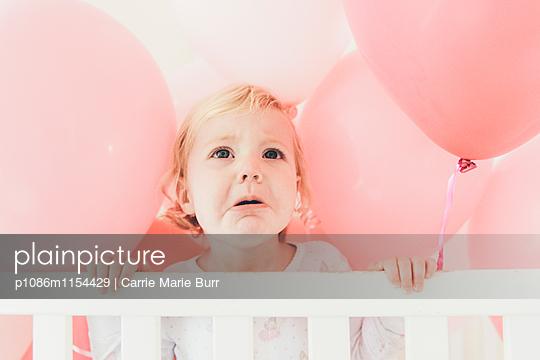 Kleines Mädchen weint zwischen Luftballons - p1086m1154429 von Carrie Marie Burr