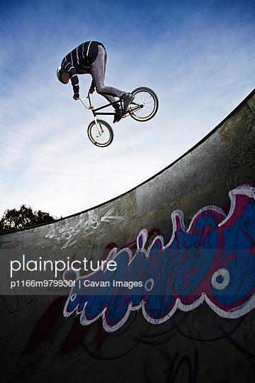 BMX Rider Jumping In Skate Park