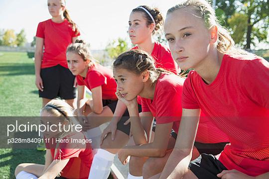 Girls soccer team sitting on bench.