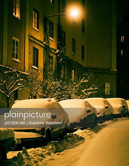 Snow-covered cars on a street