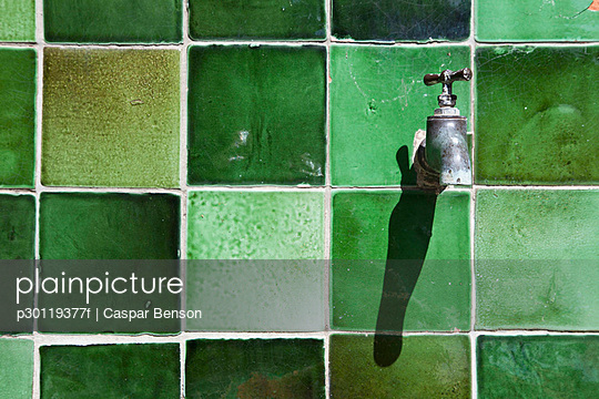 A tap on a green tiled wall