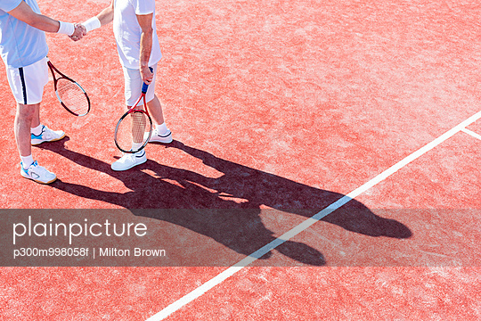 Two tennis players shaking hands on tennis court