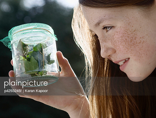 Girl holding jar of insects