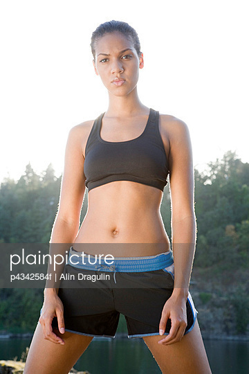Athletic jogger in sportswear standing in remote area