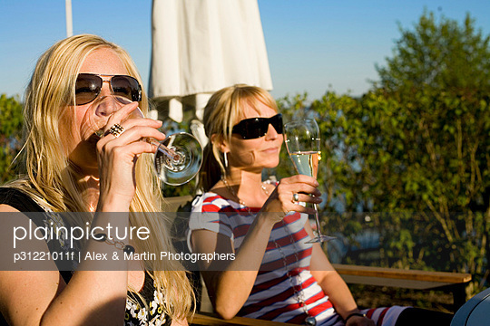Two women drinking wine in the sun Sweden.