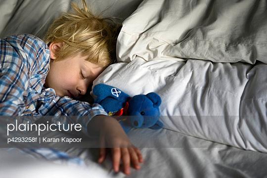 Boy asleep with teddy bear
