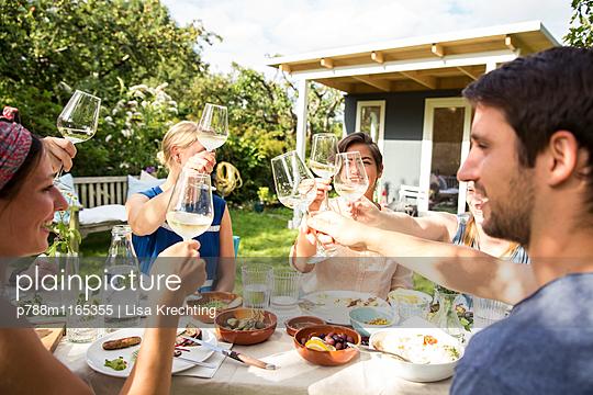 Freunde stoßen an mit Weißwein  - p788m1165355 von Lisa Krechting