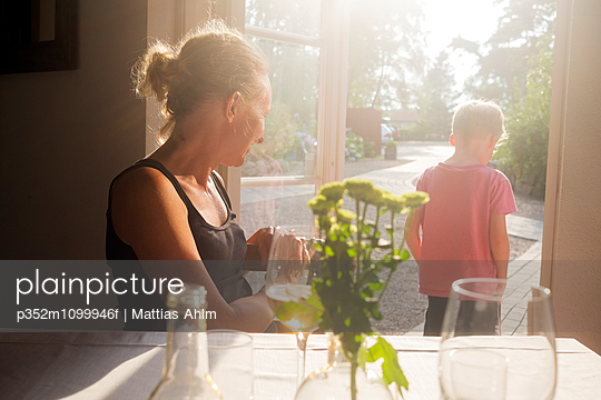 Sweden, Skane, Kullaberg, Mother looking at son (6-7) standing in doorway to backyard at restaurant