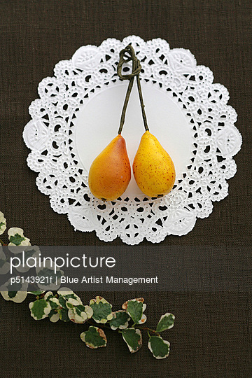 Ornaments of pear on paper lace, black background