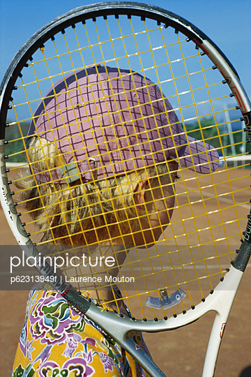 Girl holding tennis racket looking at tennis court
