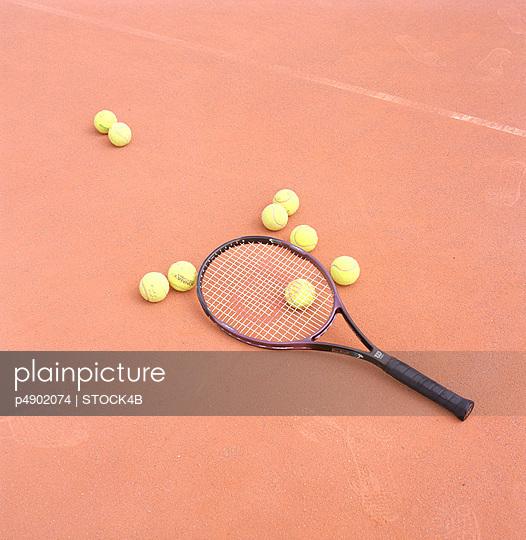 Tennis Balls and Tennis Racket on Tennis Court