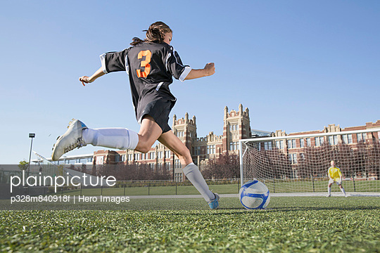 Girl soccer player about to kick ball at goalie.