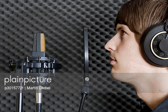 Man in sound booth of recording studio
