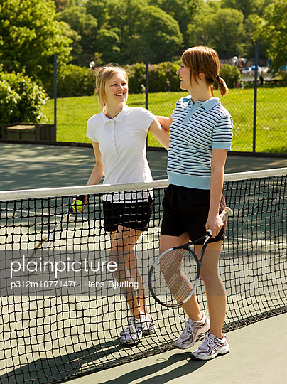 Two women in tennis court smiling at each other