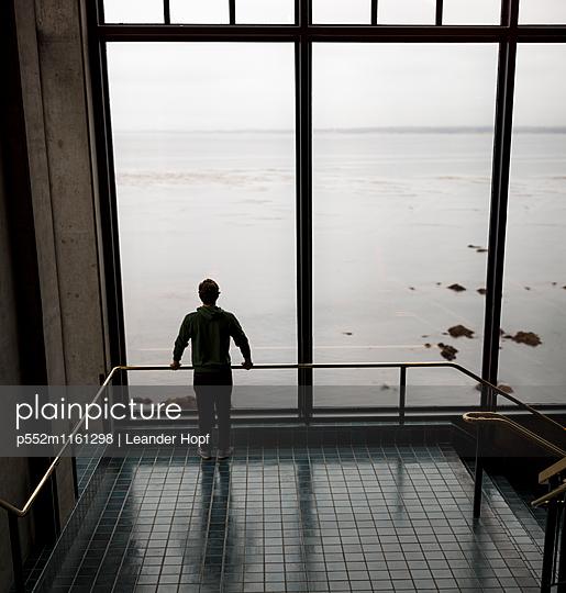 Junger Mann blickt aufs Meer - p552m1161298 von Leander Hopf
