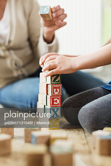 Cropped image of teacher and student stacking blocks