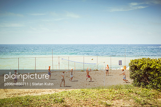 Young people are playing beach volleyball on a pitch by the sea