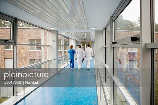 Three healthcare workers walking along a corridor