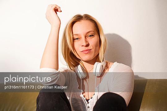 Junge Frau sitzt auf dem Sofa und träumt - p1316m1161173 von Christian Kasper