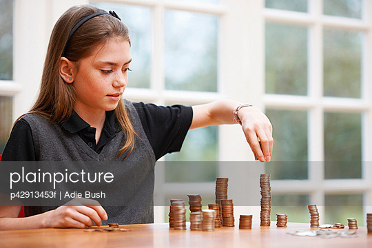 Girl counting piles of money