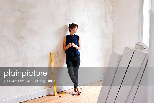 Junge Frau in neuer Wohnung - p1124m1160240 von Willing-Holtz
