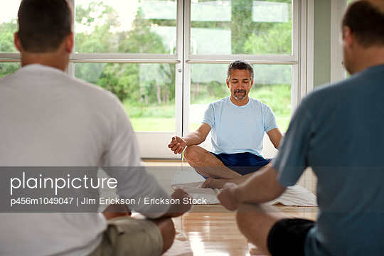 Relaxed middle-aged man teaching a meditation class at a heath spa