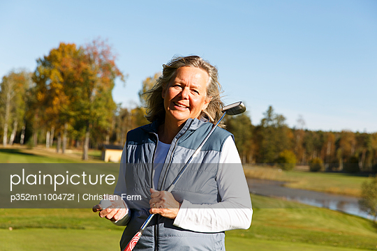 Sweden, Sodermanland, Outdoor portrait of mature woman holding golf club and golf ball