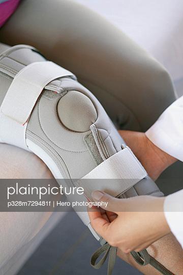 Doctor fastening knee brace on patient.