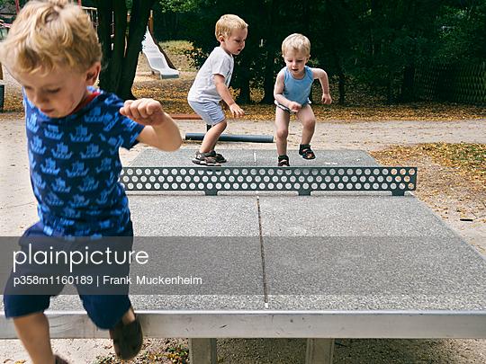 Drei Jungs klettern auf einer Tischtennisplatte herum - p358m1160189 von Frank Muckenheim