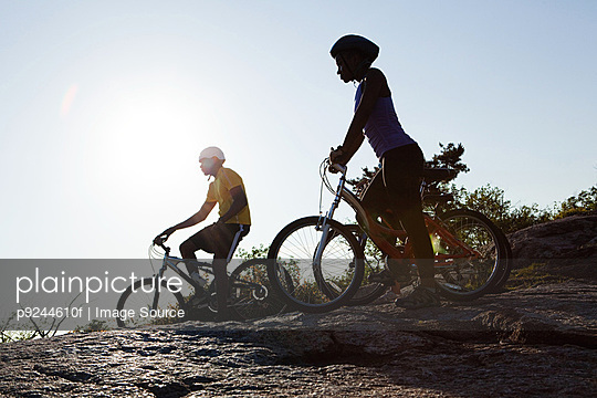 Two cyclists in rural scene, silhouette