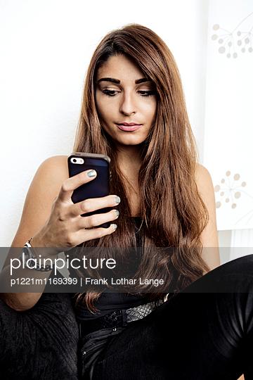 Junge Frau mit Smartphone - p1221m1169399 von Frank Lothar Lange