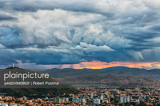 The skies turn stormy over the skies of Cochabamba, with El Cristo seen on the mountain in the middle of the city; Bolivia