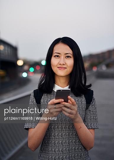 Junge Asiatin mit Smartphone  - p1124m1169918 von Willing-Holtz