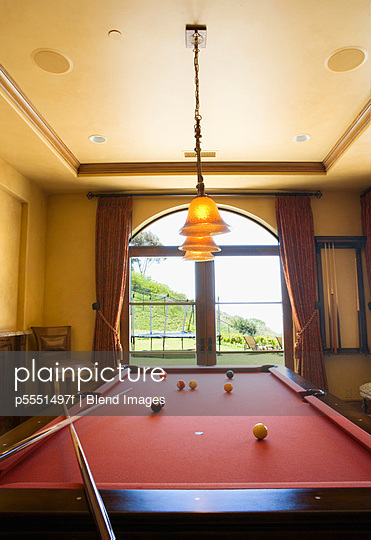 Red Pool Table and Balls with Overhead Lights and Window