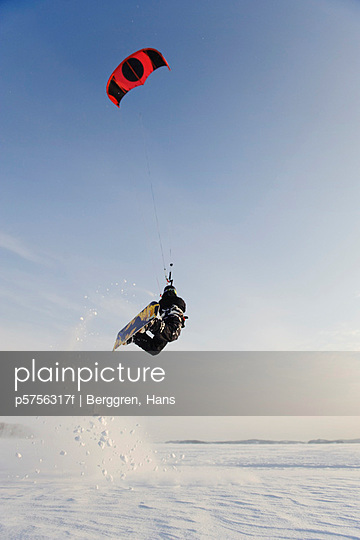 Man jumping in mid air while kiteboarding in snow