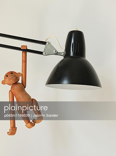Holzaffe hängt an Schreibtischlampe - p045m1169539 von Jasmin Sander