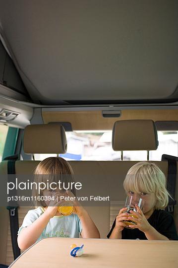 Zwei Mädchen sitzen im Wohnmobil und trinken Orangensaft, Bayern, Deutschland - p1316m1160394 von Peter von Felbert