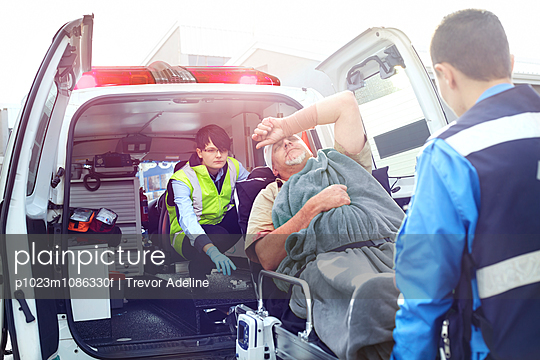 Rescue workers loading car accident victim into back of ambulance